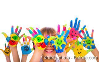 Kind mit vielen bunt bemalten Händen vor dem Gesicht