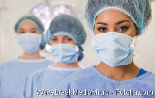 Medical students in operating theater looking at camera