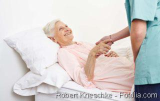 Seniorin liegt im Krankenbett