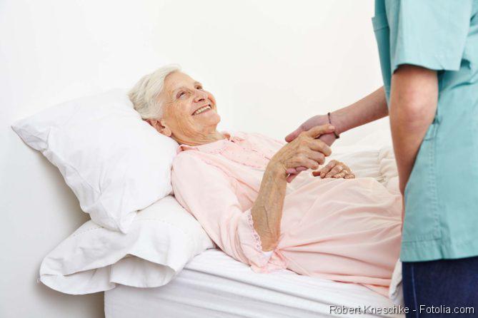 Seniorin im Pflegebett mit