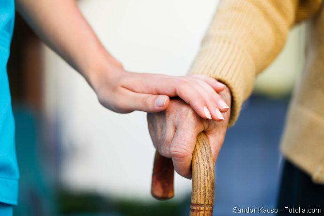 Pflege von Angehörigen, Altenpfleger, Senior mit Gehstock in der Hand
