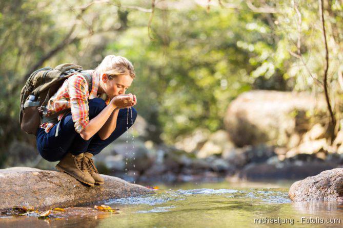 Junge Wanderin sitzt in der Hocke am Bach in den Bergen und trinkt Wasser